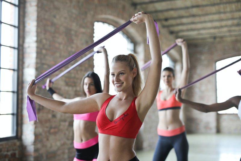 Drei Frauen machen Übungen mit einem Fitnessband
