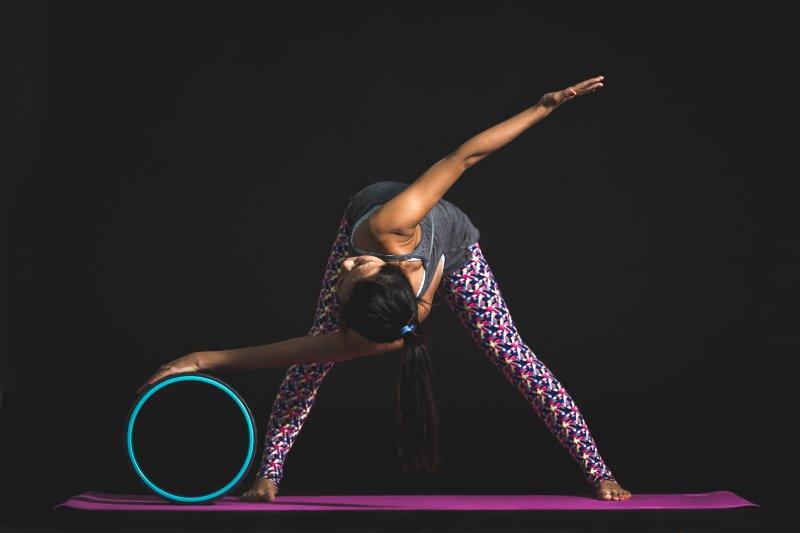 Frau dehnt sich auf einer Yogamatte