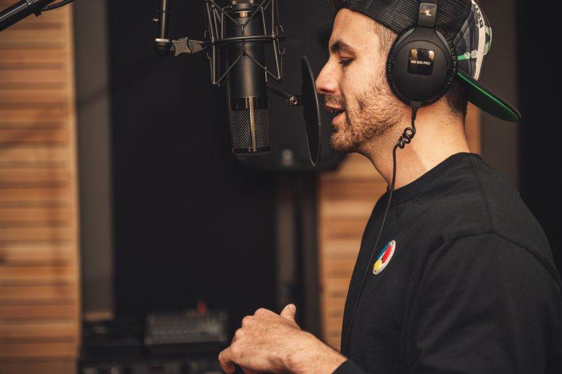 Mann mit schwarzem t-shirt und Kopfhörern bei der Arbeit