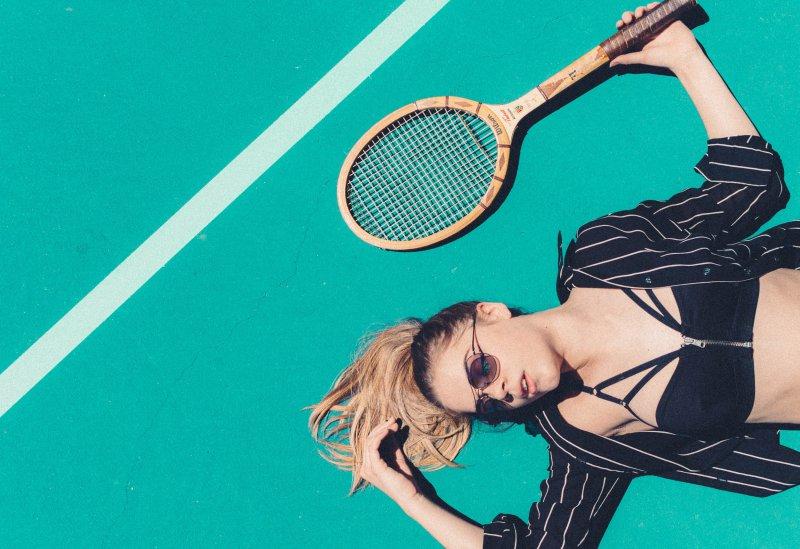 Frau liegt mit Tennisschläger auf türkisem Boden