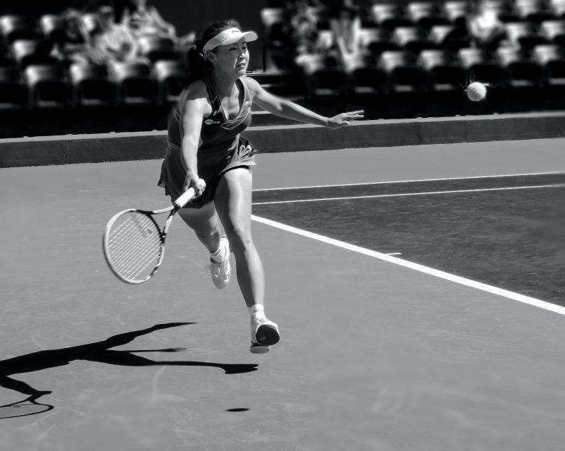 Frau läuft mit Tennisschläger zu einem Tennisball (schwarz-weiß)