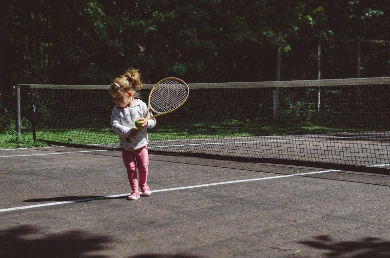 Kleines Mädchen mit einem Tennisschläger an einem Netz