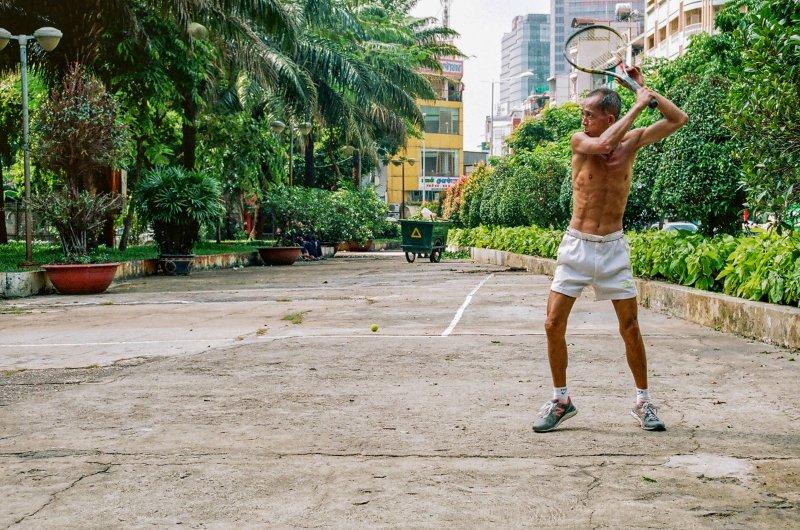 Mann hält zum Schlag einen Tennisschläger draußen über seinem Kopf