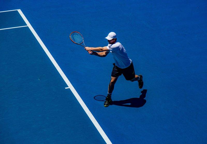 Mann hält einen Tennisschläger auf einem blauen Feld