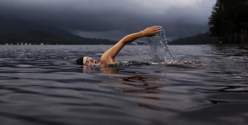 Im See mit Sportkopfhörern schwimmen