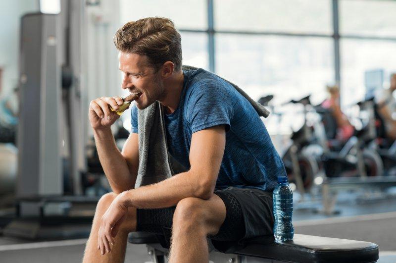 Sportlicher Mann isst einen Proteinriegel