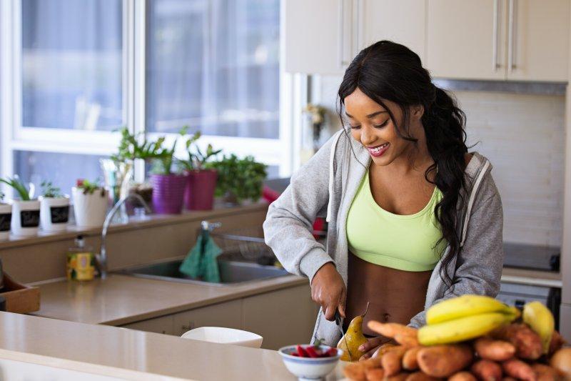 Sportliche Frau bereitet sich was zu essen zu