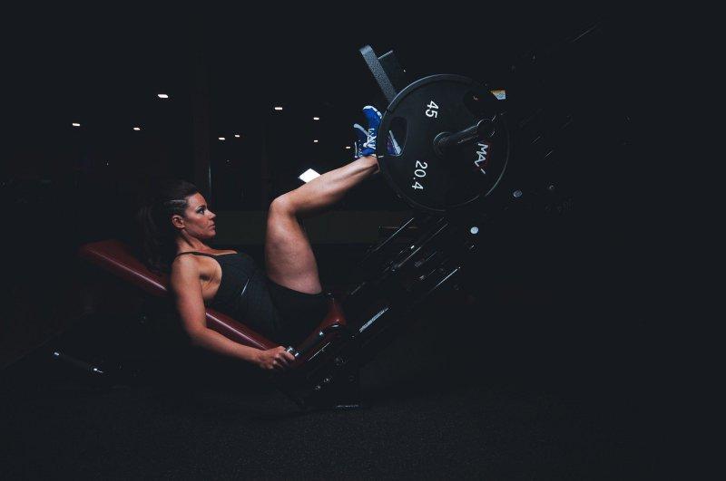 Eine Frau trainiert ihre Beine mit Gewichten