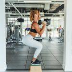 Frau trainiert mit Hanteln und Kniebeugen