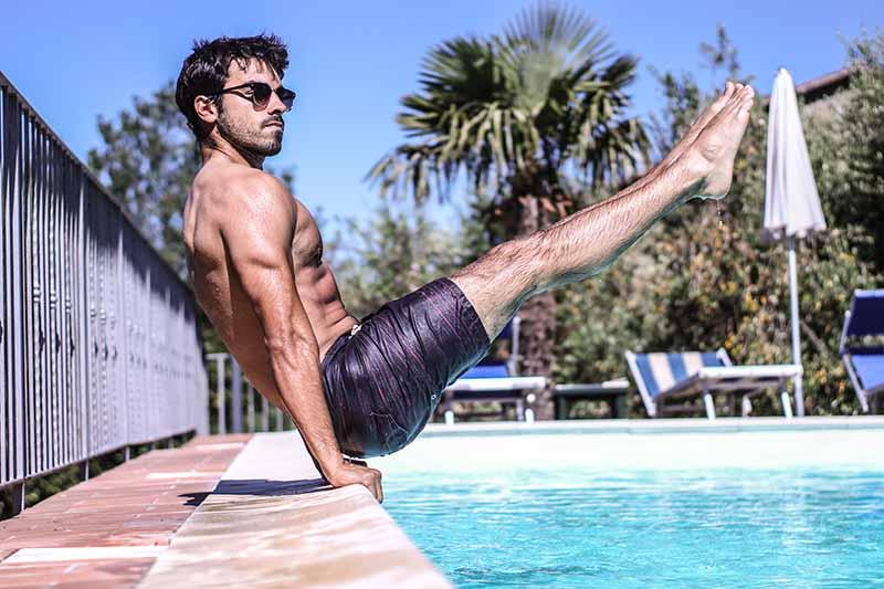 Kreatin Mann macht eine Halteposition Calisthenics am Pool Outside
