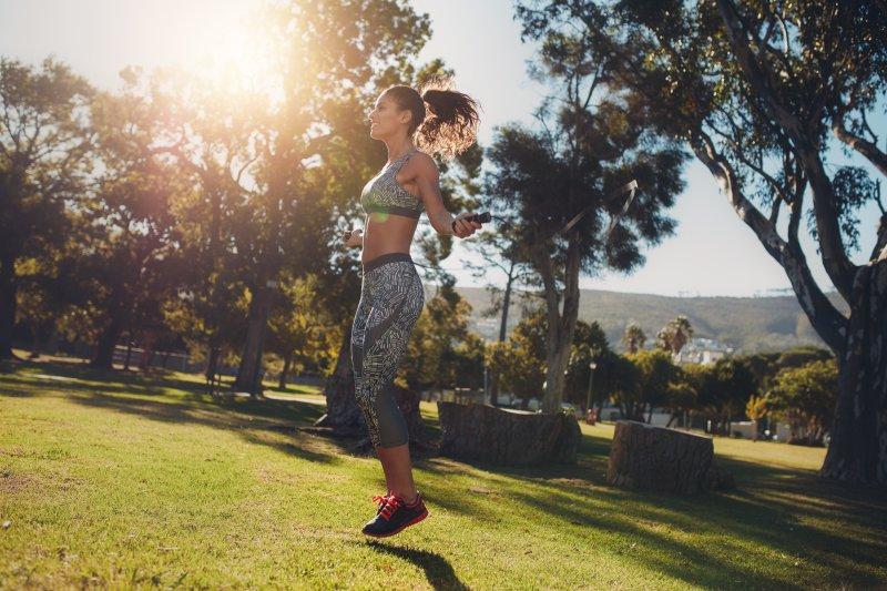 Frau trainiert draußen mit Springseil