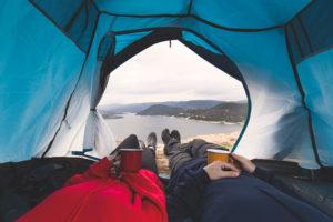 Wanderer auf Feldbett in Zelt