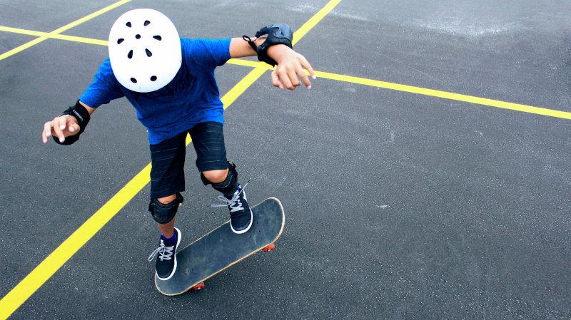 Kind mit Helm auf Skateboard