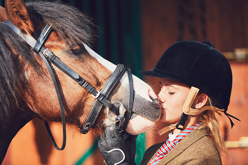 Mädchen mit Reithelm und Pony