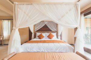 Ein Bett mit kastenförmigem Moskitonetz