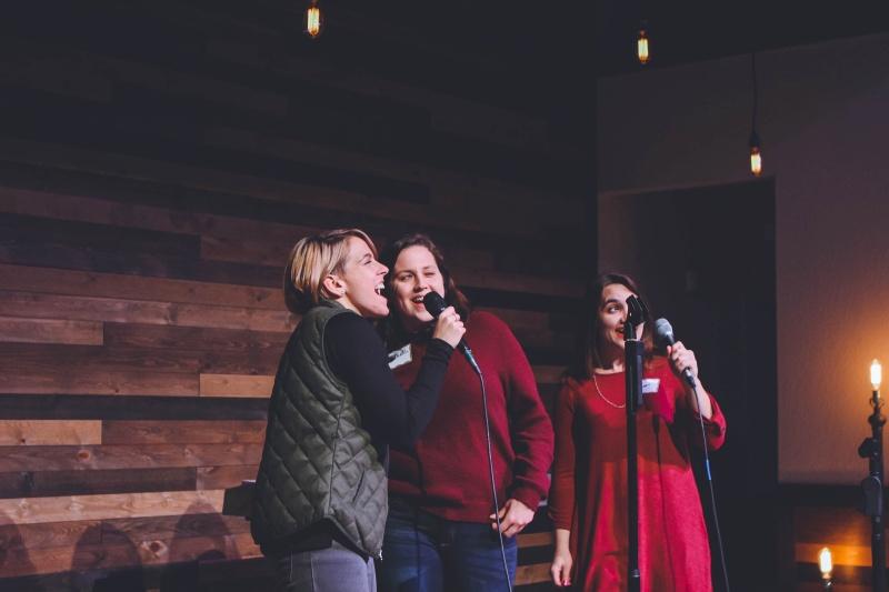 Drei Damen die Karaoke singen mit einer Karaoke-Maschine