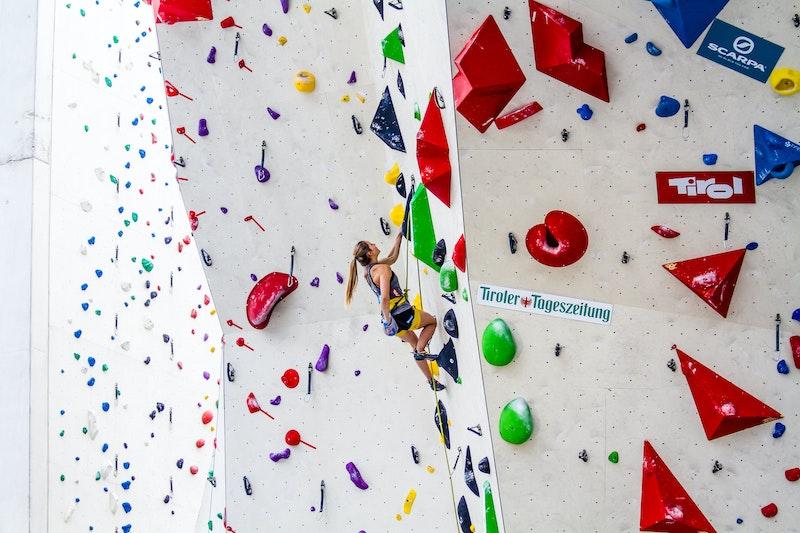 Frau klettert in der Halle mit Kletterschuhen