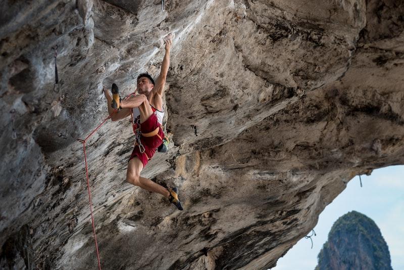 Kletterer mit Kletterschuhen mit Vorspannung und Downturn am Fels