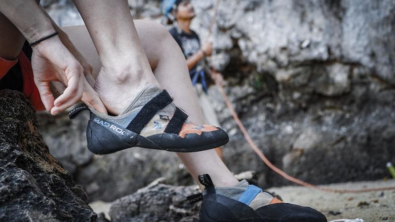 Kletterer zieht Kletterschuhe an