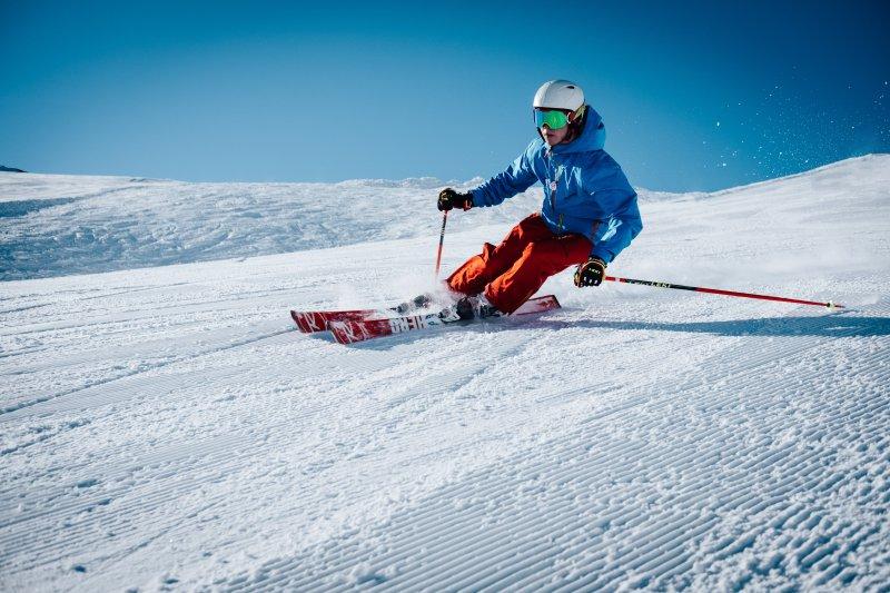 Skifahrer, der eine Skibrille mit Sehstärke trägt, fährt eine Abfahrt runter.