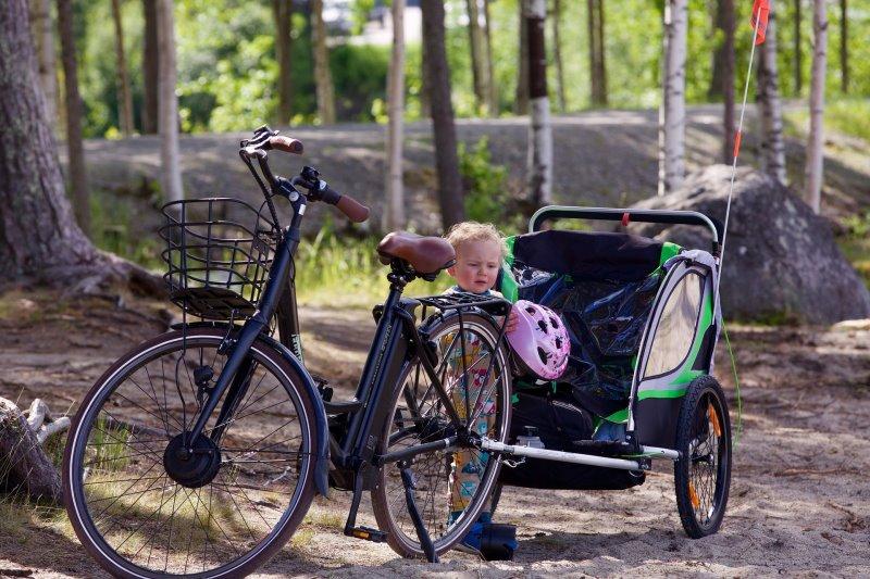 Das Kind im Fahrradanhänger mit dem Kinderfahrradhelm