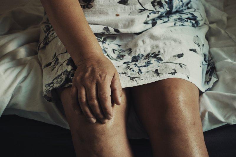 Frau hält Knie fest