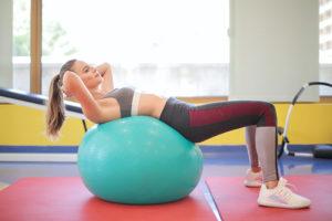 Frau trainiert mit einem Gymnastikball