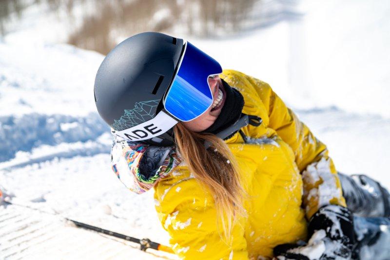 Lachende Frau beim Skifahren trägt eine Skibrille.