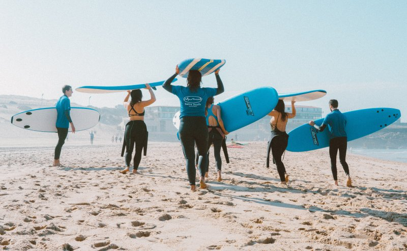 Surfer mit Wetsuits am Strand