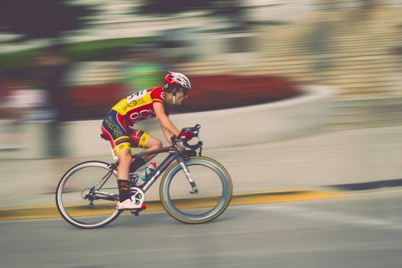 Rennradfahrer der sehr schnell in die Kurve fährt