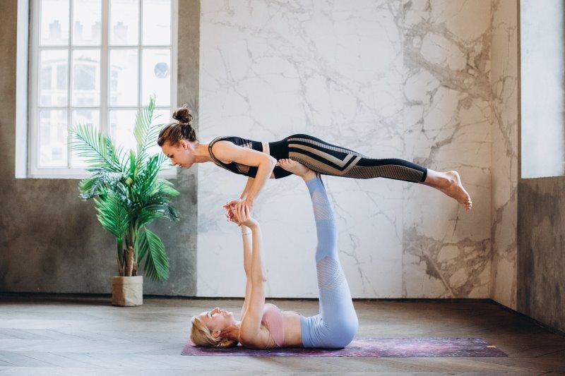 Frauen führen den Flieger als Übung des Acro Yogas aus