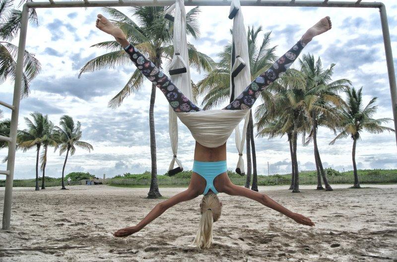 Frau praktiziert Aerial Yoga am Strand
