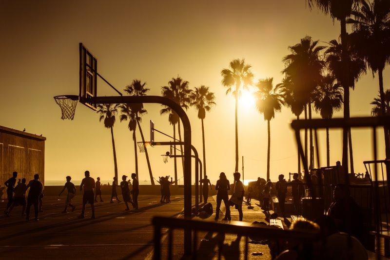 Basketball spielen während des Sonnenuntergangs