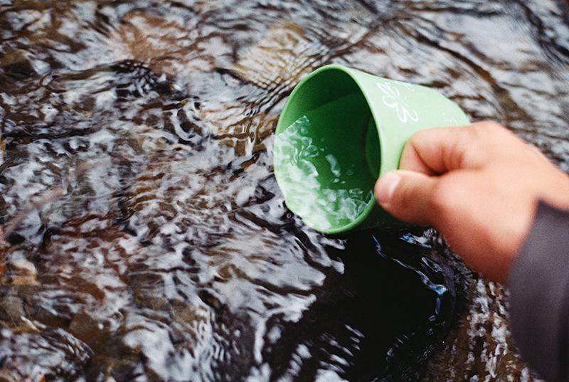 Ein Trinkbecher wird mit Wasser aus einem See aufgefüllt