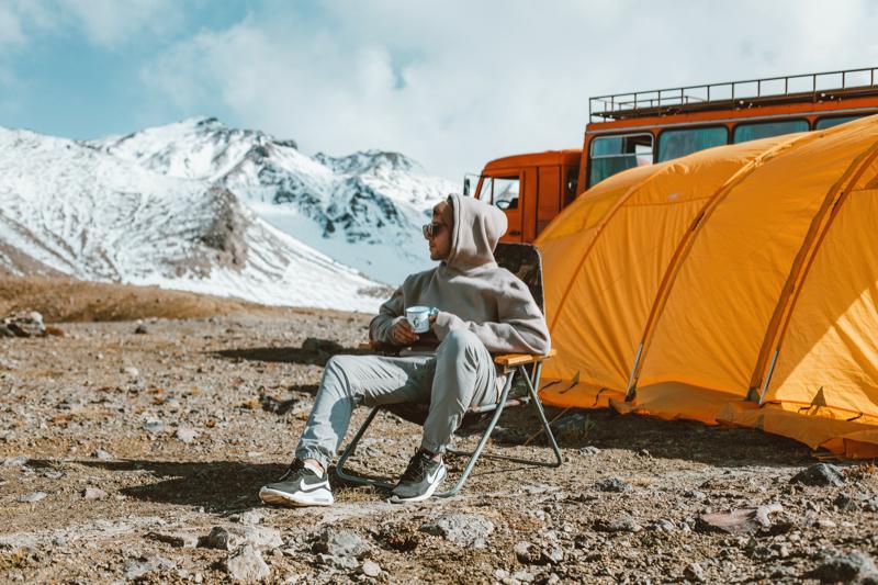Mann sitzt auf Campingstuhl vor seinem Zelt