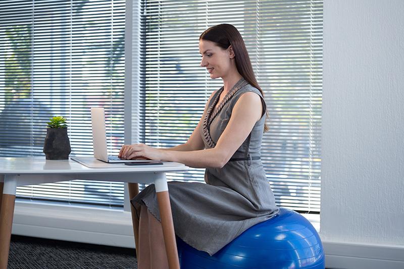 Frau sitzt auf blauem Gymnastikball am Schreibtisch