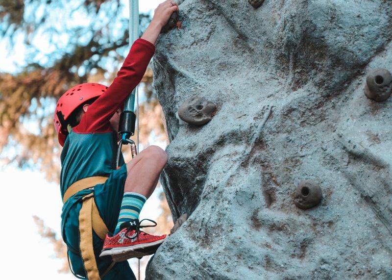 Jugendlicher klettert mit Kletterhelm