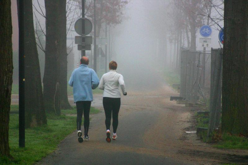 Älteres Ehepaar ist in Laufjacken im Nebel joggen