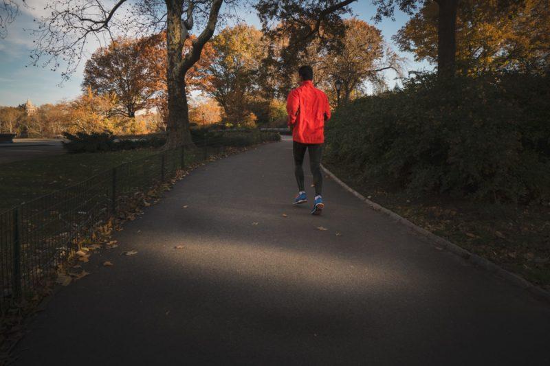 Mann in roter Laujfacke im Park