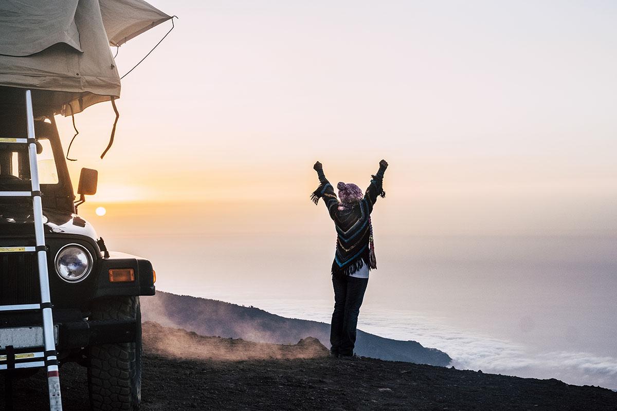 Frau mit Pickupzelt auf einer Klippe
