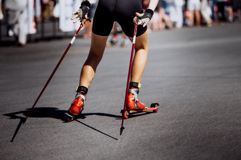 Skiroller-Fahrer in der Skating-Technik mit Stöcken und Schuhen im Fokus