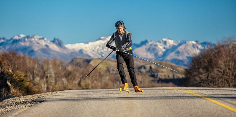 Skiroller-Läufer im Skating-Stil mit Schutzausrüstung vor einer Berglandschaft