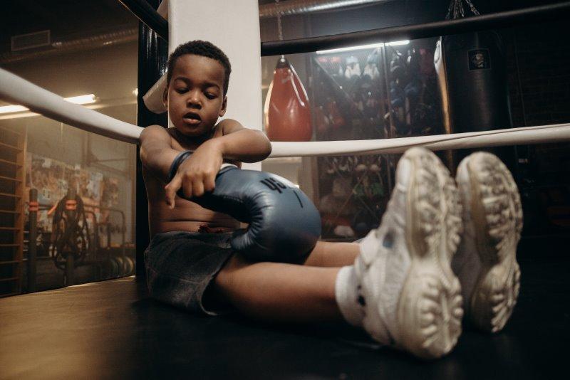Im Boxring sitzender Junge zieht Boxhandschuhe für Training am Standboxsack an