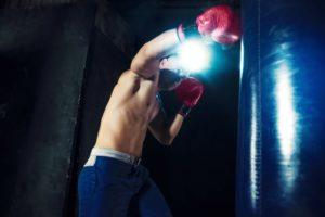 Standboxsack Test während des Trainings eines oberkörperfreien Boxers