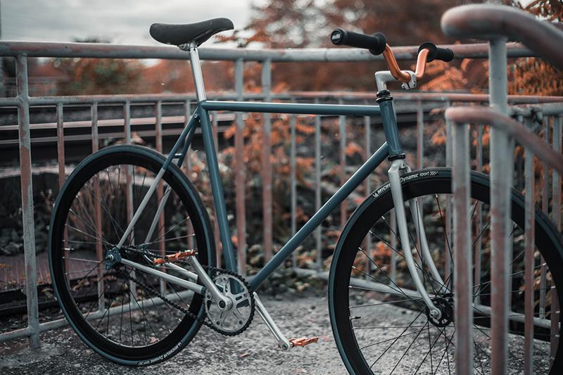 türkises SingleSpeed-Bike steht zwischen Geländergittern