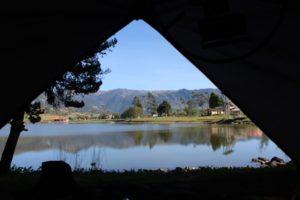 Aussicht auf einen See aus dem Inneren eines Zeltes mit schwarzer Schlafkabine