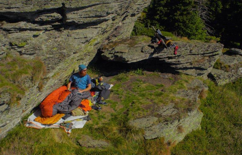 Mann sitzt in seinem Schlafsack an einer Felswand