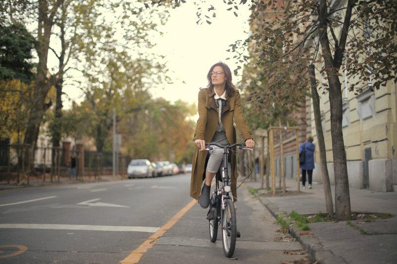Eine Frau fährt mit ihrem E-Bike-Faltrad im alltäglichen Straßenverkehr