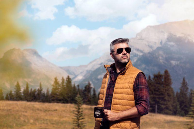 Weste tragender Mann vor Bergpanorama