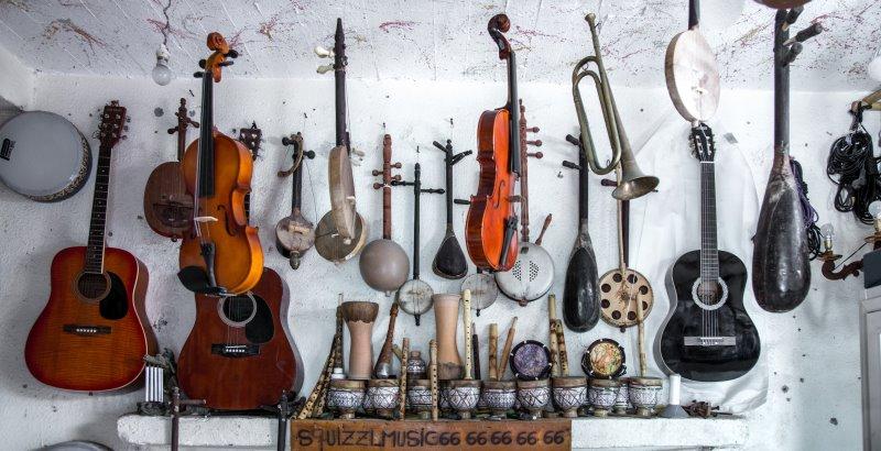 Bild mit verschieden Instrumenten, die an einer Wand aufgehängt oder gestellt sind.